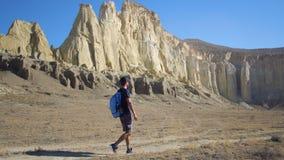 Een jonge reiziger loopt langs een weg op een bergachtig gebied Stock Foto