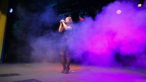 Een jonge roodharigezanger met een microfoon in haar dient een zwarte kleding in zingt op het stadium in de volledige groei stock video