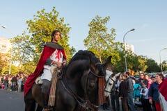 Een jonge ruiter op haar paard in middeleeuwse kleding tijdens de viering van Heilige George en de draak stock foto