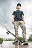 Een jonge schaatser bevindt zich met een skateboard op de achtergrond van het landschap van de stad Stock Afbeelding