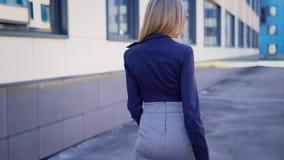 Een jonge secretaresse met een goed cijfer keert naar het werk in de bedrijf` s zaken terug na een middagpauze, die binnen plaats stock video