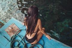 Een jonge sexy Filipijnse meisjeszitting op een vissersboot met haar zwart zwempak die van de oceaanwind in de Filippijnen geniet stock fotografie