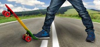 Een jonge skateboarder in tennisschoenen en jeans, die zich op zijn vleet bevinden Close-upfragment van het skateboard en de voet royalty-vrije stock afbeeldingen