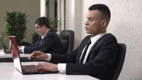 Een jonge succesvolle Afrikaanse mannelijke zakenman die in het bureau aan vermoeid laptop werken die, zijn hoofd, een hoofdpijn  stock videobeelden