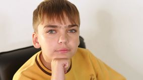Een jonge tienerjongen in een gele sweater zit als leer zwarte voorzitter in de Studio stock footage
