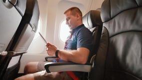 Een jonge toerist op het vliegtuig werkt met de tablet alvorens weg te gaan stock footage