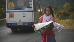 Een jonge toerist zoekt een weg, bestuderend de kaart van Altai tijdens de reis stock video