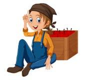 Een jonge tuinmanzitting naast de doos Stock Foto's
