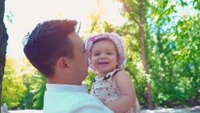 Een jonge vader houdt een kleine dochter in zijn wapens en kust haar tegen de achtergrond van groene bomen stock videobeelden