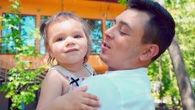 Een jonge vader houdt een kleine dochter in zijn wapens en kust haar tegen de achtergrond van het huis stock videobeelden