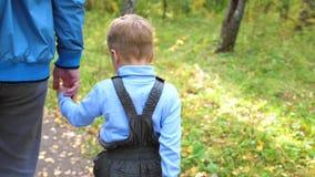 Een jonge vader loopt in het de herfstpark met zijn kind De vader houdt zijn zoons` s hand Autumn Landscape stock footage