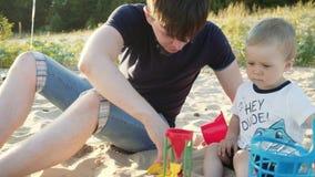 Een jonge vader met een jonge zoon op strand het spelen met kinderen` s speelgoed stock footage