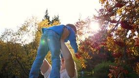Een jonge vader speelt met een kind, houdt hem vast in zijn armen, werpt op De zon komt door het kind. Het lachen stock video