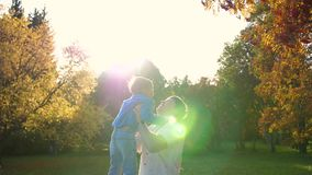 Een jonge vader speelt met een kind, houdt hem vast in zijn armen, werpt op De zonnestralen door het kind Het lachen stock footage