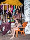 Een jonge verkoopster weeft een ander jong meisje in het haar verkocht enkel ornamenten in de avond op de waterkant in de stad va stock foto's