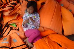 Een jonge Vietnamese meisjeszitting in een stapel van oranje reddingsvesten Stock Fotografie