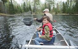 Een jonge visser in een kano glimlacht het zien van opgeleverde snoekbaarzen Stock Afbeelding