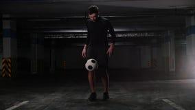 Een jonge voetbalmens die de bal schopt en het in evenwicht brengt op de voet stock videobeelden