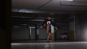 Een jonge voetbalmens opleidingstrucs met de bal Het in evenwicht brengen van de bal op de voet stock videobeelden