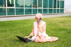 Een jonge vrij moslimonderneemster in een park terwijl het spreken op smartphone die laptop bekijken stock fotografie