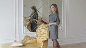 Een jonge vrouw in grijze kleding bevindt zich dichtbij de gouden stoel in studio stock footage