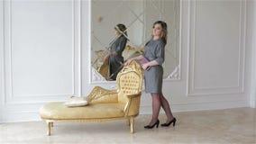 Een jonge vrouw in grijze kleding bevindt zich dichtbij de gouden stoel in studio stock video