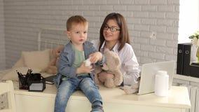 Een jonge vrouw arts die met een kleine jongen in een kliniek van kinderen in bureau spelen stock videobeelden