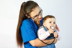 Een jonge vrouw arts houdt een baby in haar wapens en bekijkt het, en de kindspelen met een stethoscoop stock afbeelding