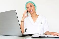 Een jonge vrouw arts With laptop in haar bureau die op de telefoon spreken royalty-vrije stock afbeeldingen