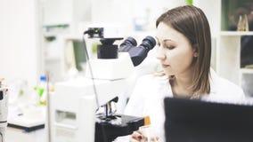 Een jonge vrouw arts zit voor de microscoop royalty-vrije stock foto