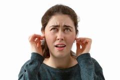 Een jonge vrouw behandelt haar oren van het lawaai Emotie van ontevredenheid en irritatie op het gezicht Ge?soleerde royalty-vrije stock afbeelding