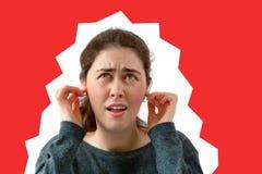 Een jonge vrouw behandelt haar oren van het lawaai Emotie van ontevredenheid en irritatie op het gezicht Rode achtergrond De ruim stock afbeeldingen