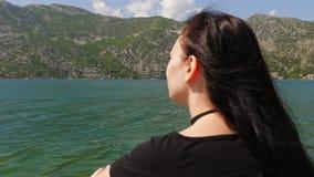 Een jonge vrouw bekijkt het water en de bergen stock footage