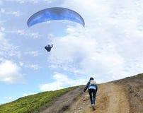 Een jonge vrouw beklimt op een berg om een glijscherm te ontmoeten die in de lucht hangen Royalty-vrije Stock Afbeeldingen