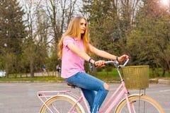 Een jonge vrouw berijdt op een fiets op de weg in het park Stock Afbeeldingen