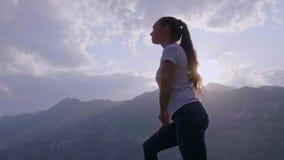 Een jonge vrouw bevindt zich bovenop een berg stock footage
