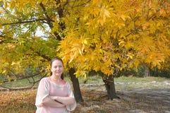 Een jonge vrouw bevindt zich door de bomen De herfst Royalty-vrije Stock Afbeeldingen