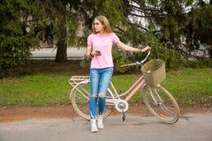 Een jonge vrouw bevindt zich met een cellphone en een fiets in Royalty-vrije Stock Foto's