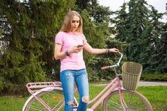 Een jonge vrouw bevindt zich met een mobiele telefoon en een fiets in t Royalty-vrije Stock Foto's