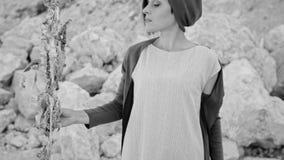 Een jonge vrouw bevindt zich tegen een achtergrond van bergen en stenen met magisch gras enchantress Zwart-wit beeld stock video