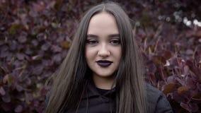 Een jonge vrouw bevindt zich tegen de achtergrond van een hoge struik en onderzoekt de camera stock videobeelden