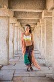 Een jonge vrouw bevindt zich tussen de kolommen Stock Foto