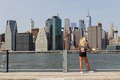 Een jonge vrouw bewondert de mening van de horizon van Manhattan Stock Foto's