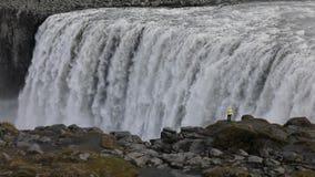 Een jonge vrouw bewondert een krachtige woedende waterval die zwaar langs een rotsachtige rand valt Een glasheldere stroom van gl stock footage