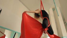 Een jonge vrouw is bezig geweest met acrobatiek op canvases stock videobeelden