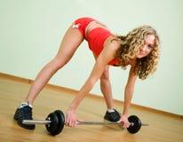 Een jonge vrouw is bezig geweest met het weightlifting Stock Afbeelding
