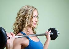 Een jonge vrouw is bezig geweest met het weightlifting Stock Afbeeldingen