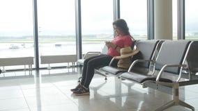 Een jonge vrouw bij de luchthaven die op vertrek wachten en smartphone bekijken stock videobeelden