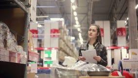 Een jonge vrouw controleert haar lijst, zoekend iets op de planken, die haar karretje in een pakhuis duwen stock footage