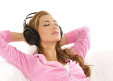 Een jonge vrouw die aan de muziek in hoofdtelefoons luistert Royalty-vrije Stock Foto